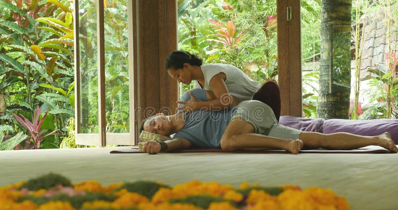 Young beautiful and exotic Asian Indonesian therapist woman giving traditional Thai massage to man relaxed at tropical wellness royalty free stock photo