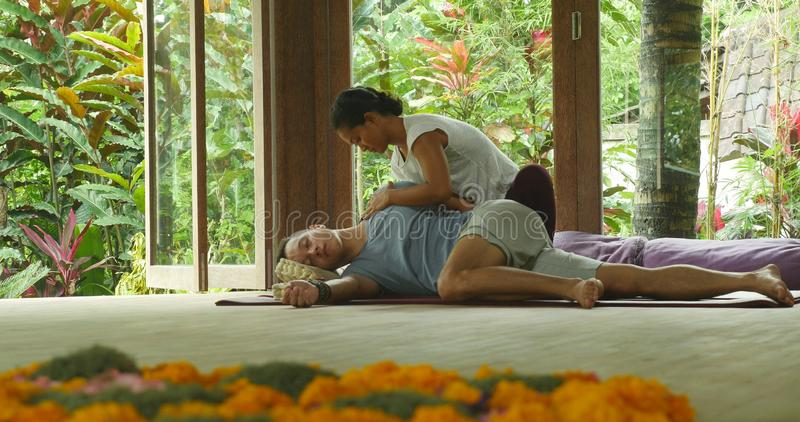 Young beautiful and exotic Asian Indonesian therapist woman giving traditional Thai massage to man relaxed at tropical wellness stock images