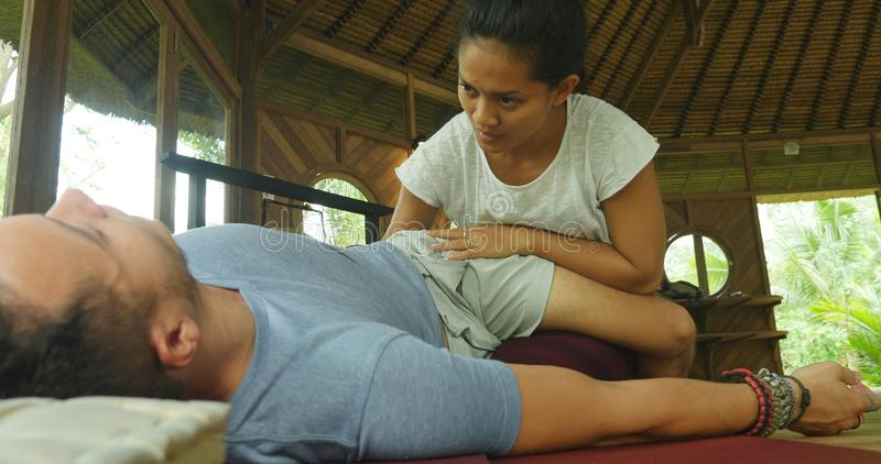 Young beautiful and exotic Asian Indonesian therapist woman giving traditional Thai massage to man relaxed at tropical wellness royalty free stock image