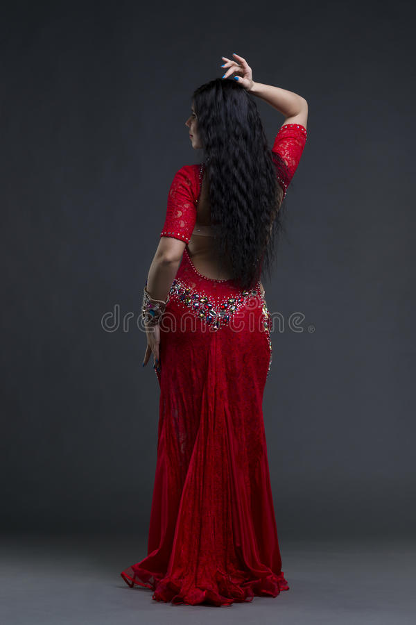Young beautiful exotic eastern women performs belly dance in ethnic red dress on gray background stock photo