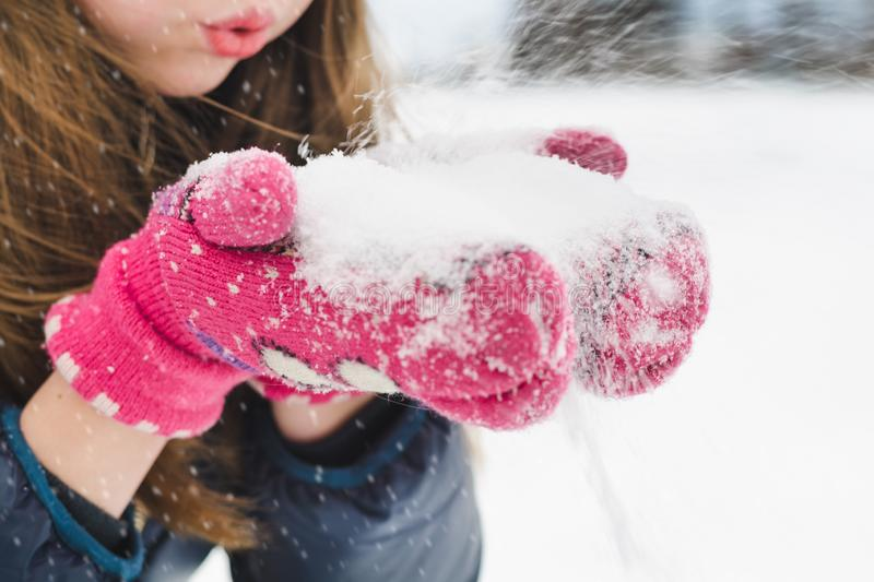 Young beautiful fair-haired girl blows snow from her hands in the park under soft fluffy snow on a cold winter day stock photo