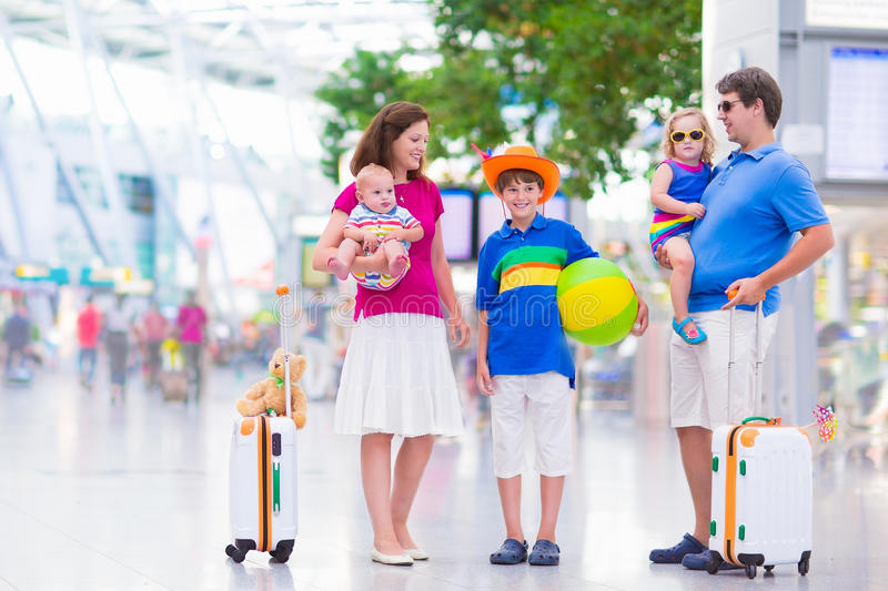 Young beautiful family at the airport. Big happy family with three kids traveling by airplane at Dusseldorf International airport, parents with teenager boy stock images