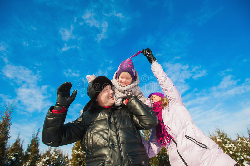 Young beautiful family in bright clothes winter fun jumping and running, snow, lifestyle, winter holidays. Young beautiful family in bright clothes winter fun stock photos