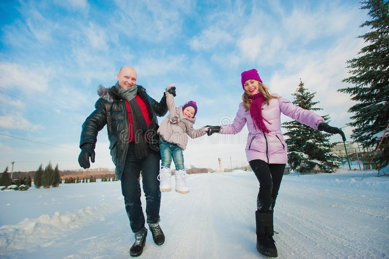 Young beautiful family in bright clothes winter fun jumping and running, snow, lifestyle, winter holidays royalty free stock images