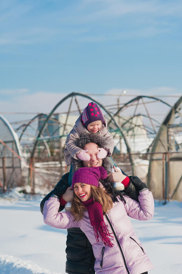 Young beautiful family in bright clothes winter fun jumping and running, snow, lifestyle, winter holidays royalty free stock image