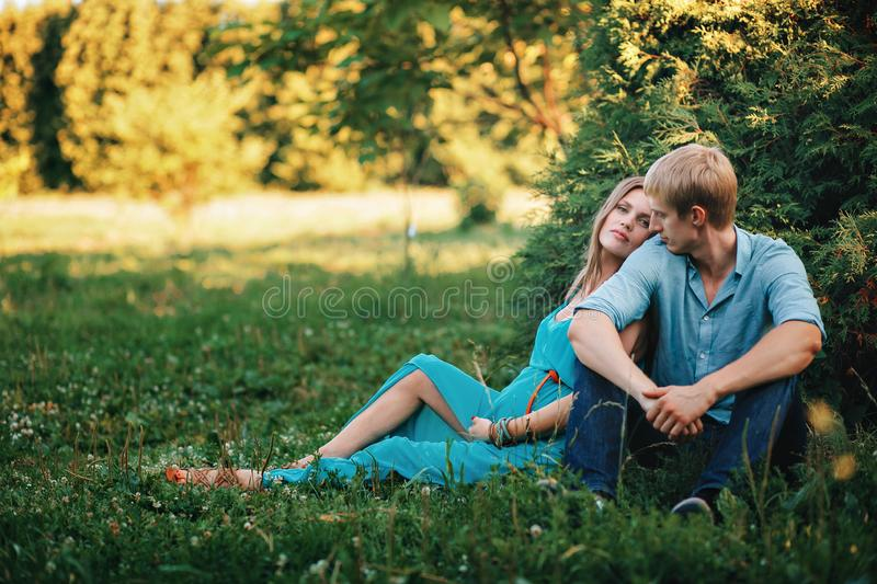 Young beautiful family, future parents. Pregnant woman in the park outdoors. Calm pregnant woman in third trimester stock photos