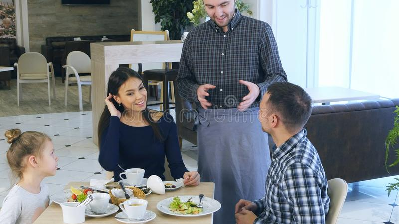 Young beautiful family have fun and dance in cafe with jolly waiter. royalty free stock photography