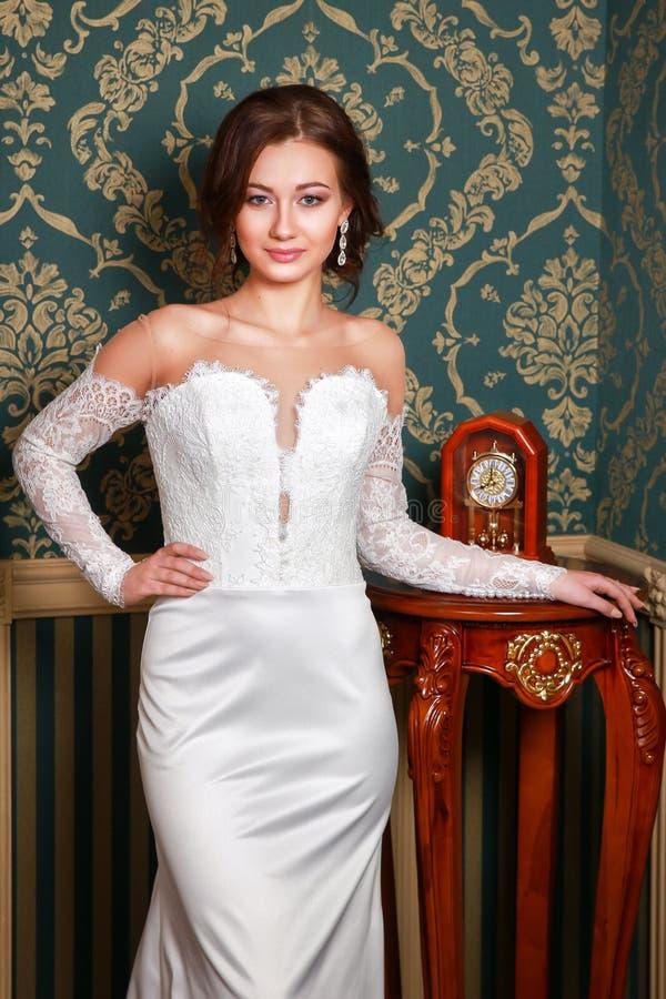 Young beautiful fashion bride posing in studio. Wedding dress. Young beautiful fashion bride posing in studio. Wedding white dress royalty free stock images