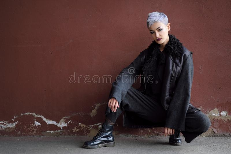 Young beautiful fashion girl shooting outdoors near brick wall at home royalty free stock images