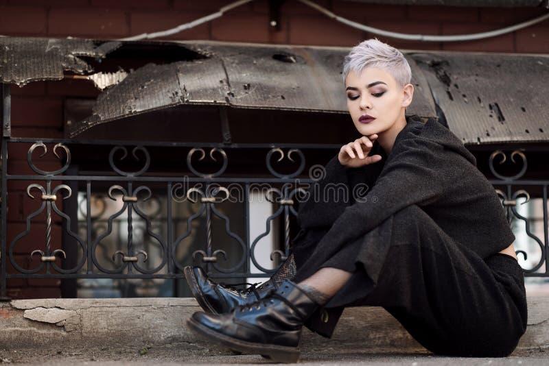 Young beautiful fashion girl shooting outdoors near brick wall at house royalty free stock photo