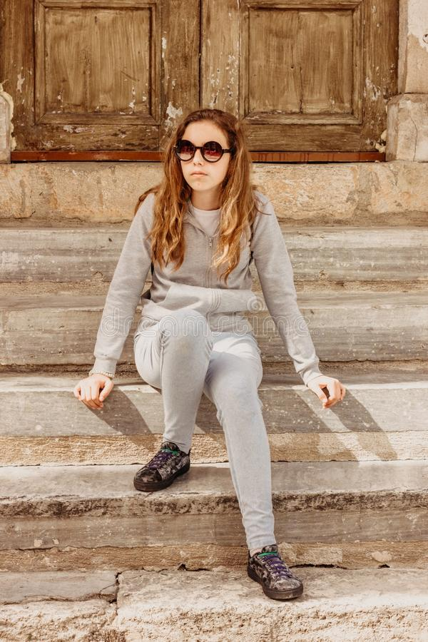 Young beautiful fashionable girl in sunglasses is sitting on the stone steps at the old wooden door in Antalya royalty free stock image