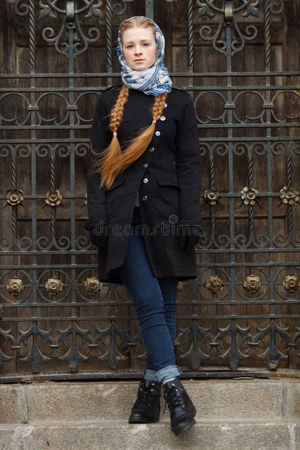Young beautiful fashionable redhead woman with braids hairdo in blue white headcraft stylish denim black trench jacket posing wrou. Young beautiful fashionable royalty free stock photo