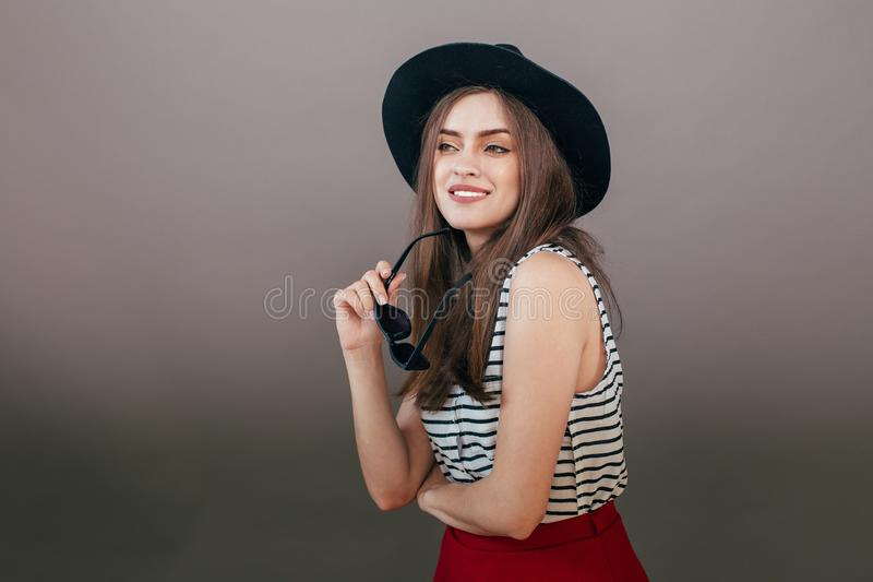 Young beautiful fashionable woman with trendy makeup in black hat and glasses on the grey background . Model looking at camera, w stock photos