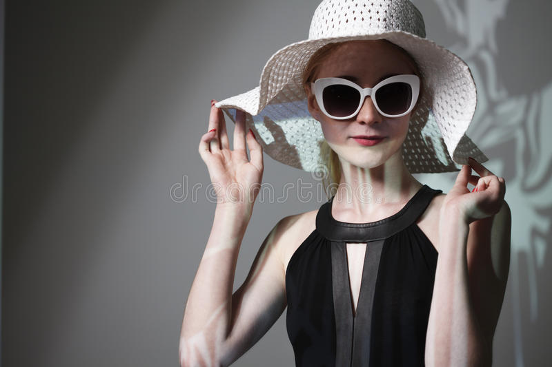 Young beautiful fashionable woman with trendy makeup. Model looking at camera, wearing stylish eyeglasses, hat. Female fashion, be stock image