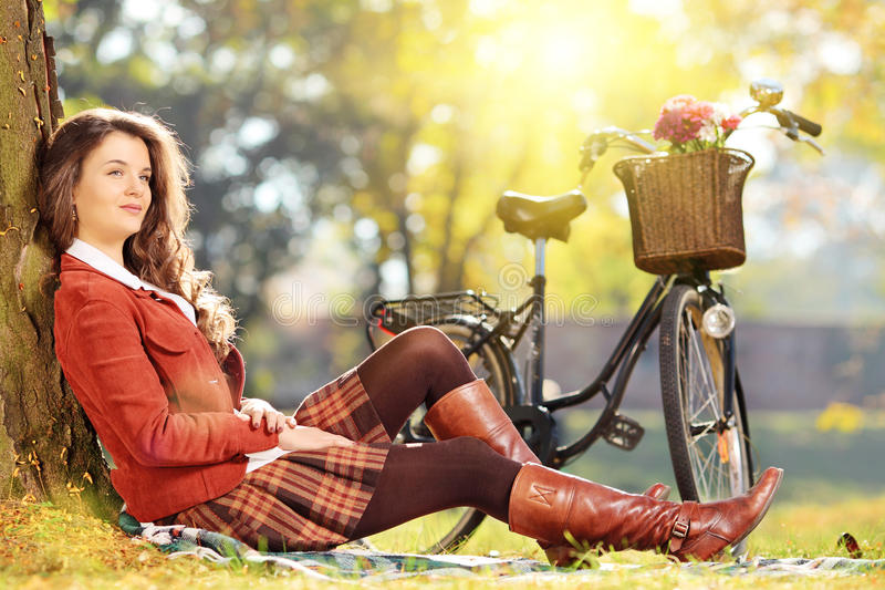Young beautiful female with bicycle relaxing in park stock photography