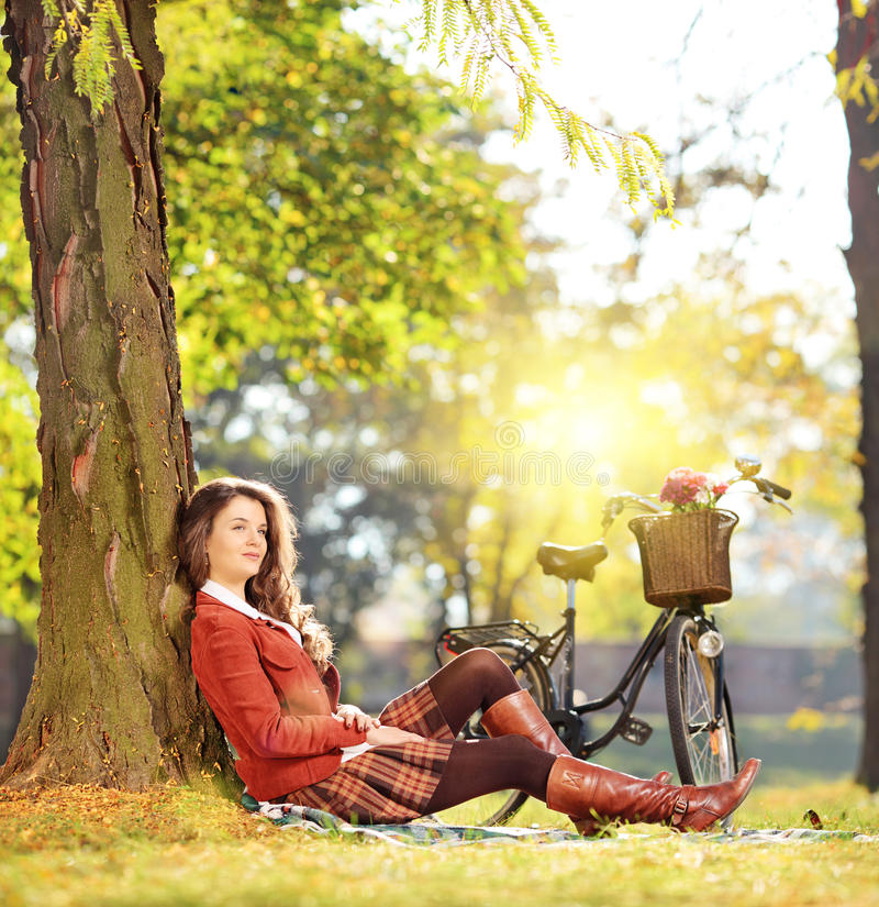 Young beautiful female with bicycle relaxing in a park on a sunny day stock photo