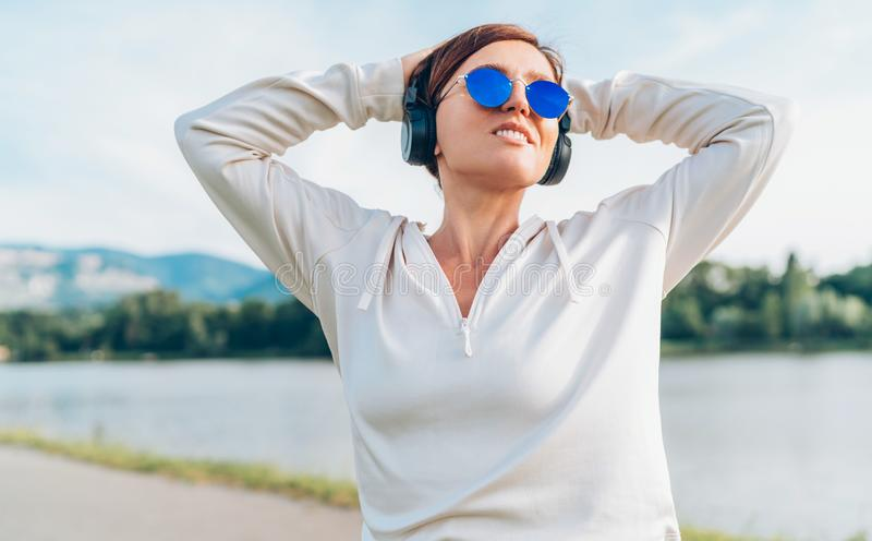 Young beautiful female in blue sunglasses listening to music using smartphone and wireless headphones cheerfully smiling. Walking royalty free stock photography