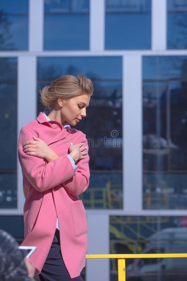 Young beautiful female is cold in thin pink coat. stock image