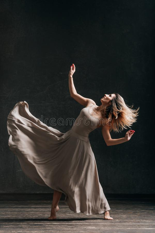 Young beautiful female dancer is posing in the studio. Young beautiful woman dancer posing in studio royalty free stock photography