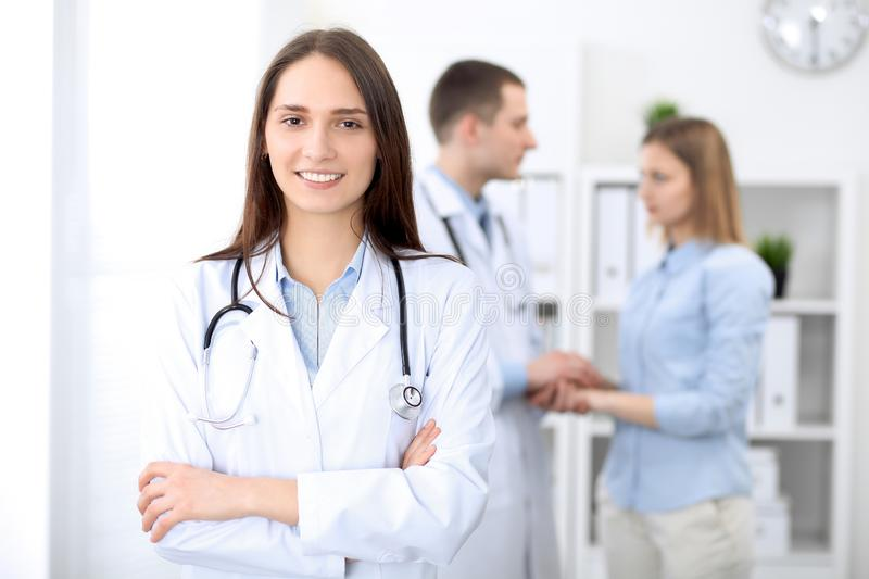 Young beautiful female doctor smiling on the background with patient in hospital stock photo