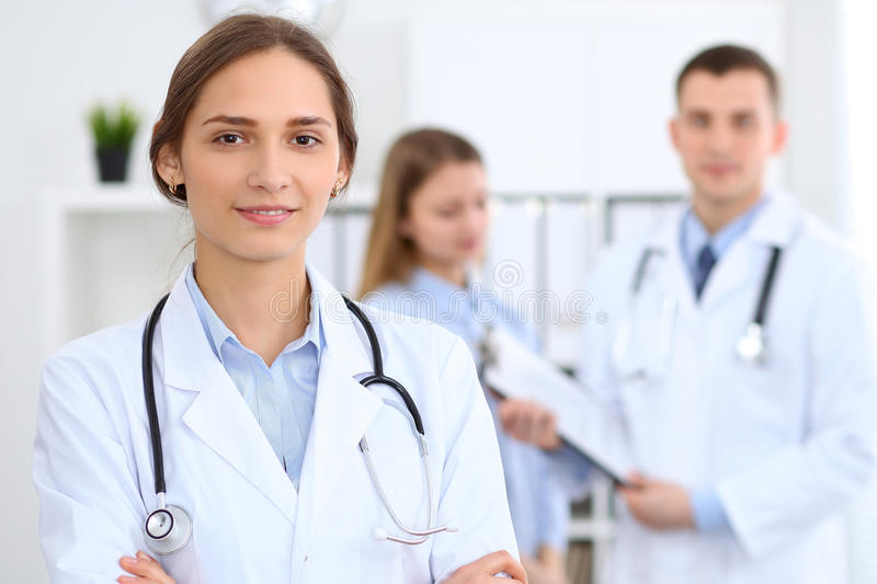 Young beautiful female doctor smiling on the background with patient in hospital stock photography
