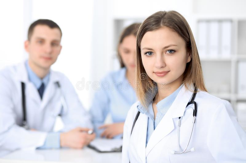 Young beautiful female doctor smiling on the background with patient in hospital royalty free stock image