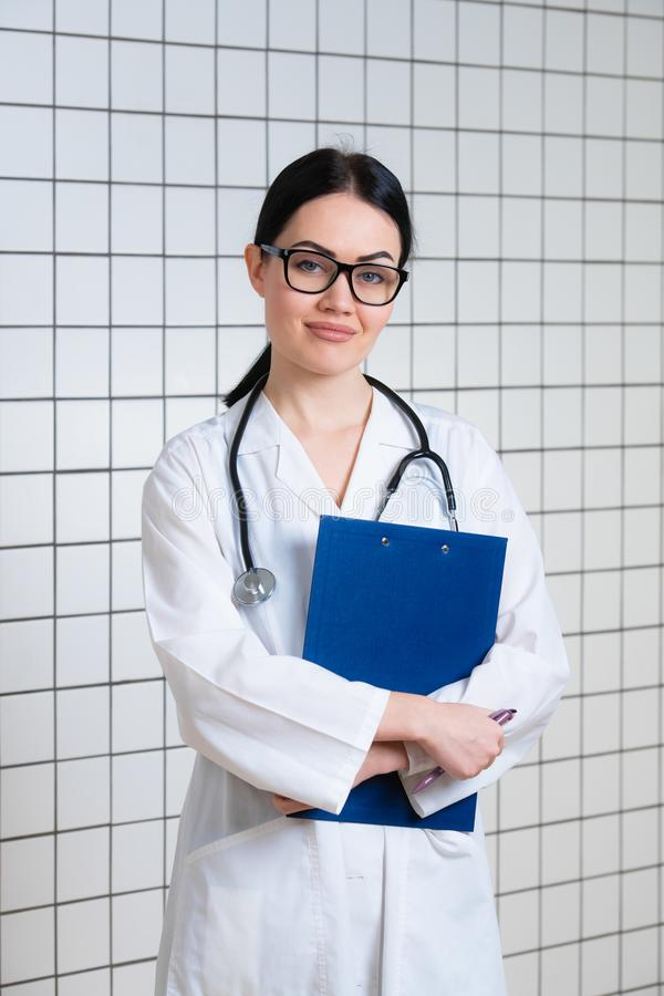 Young beautiful female doctor in white surgical coat with black stethoscope and blue paper holder in hands standing at stock photo