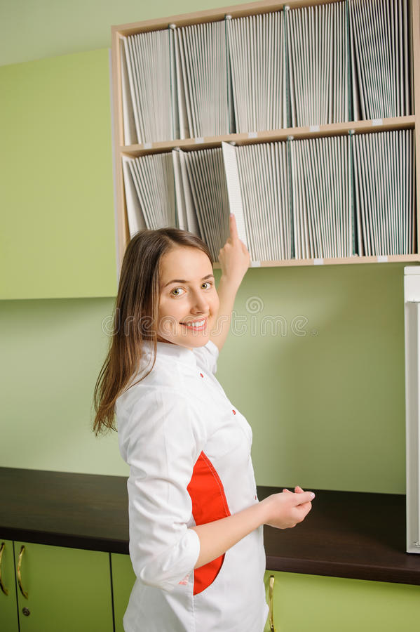 Young beautiful female doctor in white uniform. Smiling, looking to the camera and getting patient& x27;s paperwork in the hospital stock images
