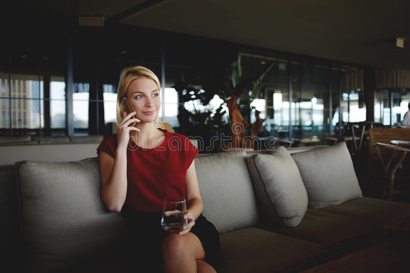 Young beautiful female entrepreneur talking on mobile smart phone while sitting with glass of fresh water in modern restaurant, royalty free stock photo