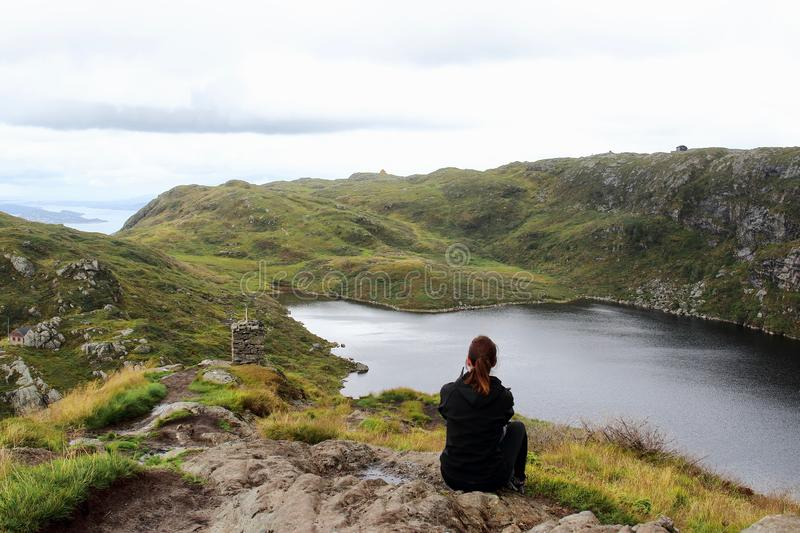 Young beautiful female hiker resting in front of a lake during the `vidden` trail, a very famous route between Ulriken and Floyen stock image
