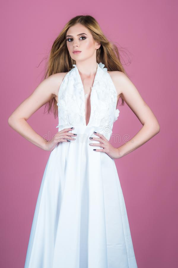 Young beautiful female model in white dress on pink background. studio woman with brunette hair and makeup. clothes stock photography