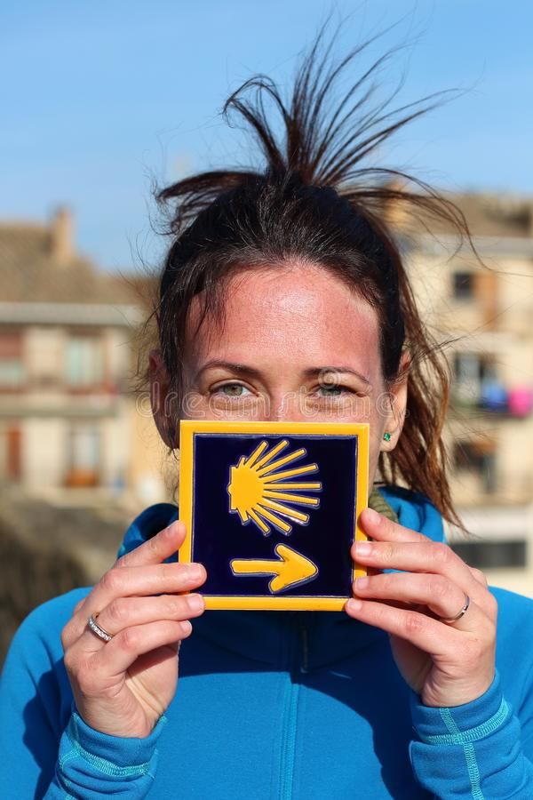 Young beautiful female pilgrim`s portrait posing with the typical `Camino de Santiago` blue tile painted with a yellow shell stock photography