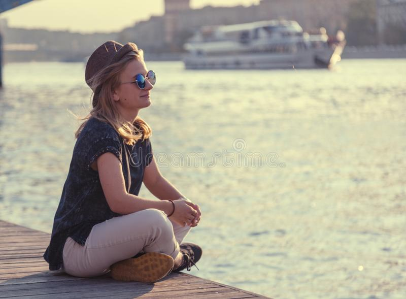 Young beautiful female student girl in hat and sunglasses resting on the pier overlooking the river, evening city and boat stock photography