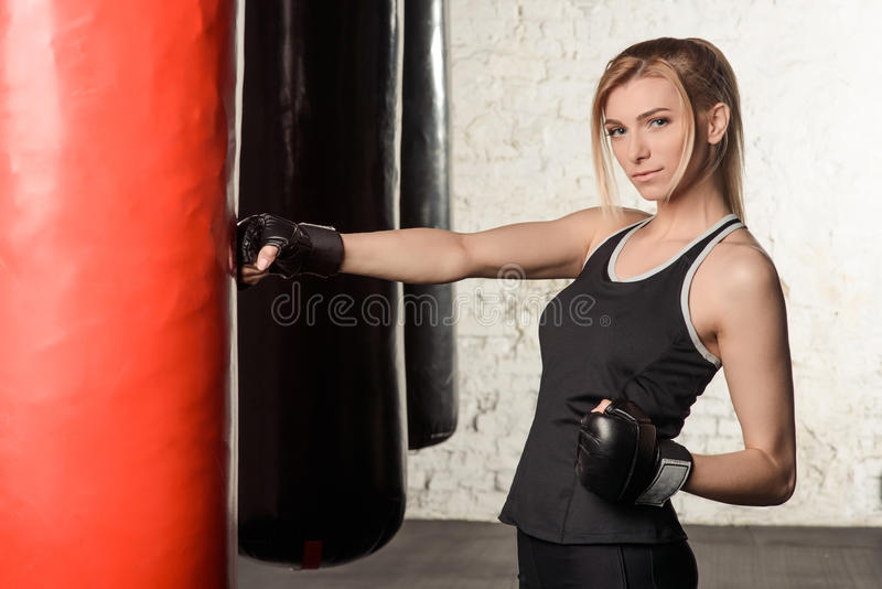 Young, beautiful and fit blond lady is working out in a loft gym. She is wearing black sport tank top and boxing gloves. The lady looks serious showing off her stock photography