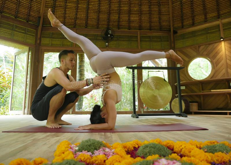 Young beautiful and fit woman with acrobat man as yoga coach learning balance posture in acroyoga workout at exotic fitness studio stock photography