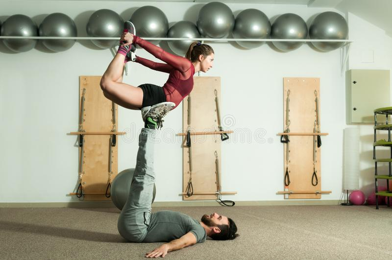 Young beautiful fitness couple workout extreme acrobatic exercise as preparation for the competition, selective focus royalty free stock photography