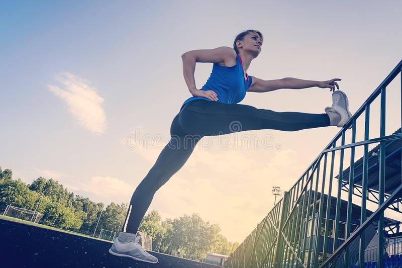 Young beautiful fitness girl doing stretching at stadium. Sports, health care concept stock images