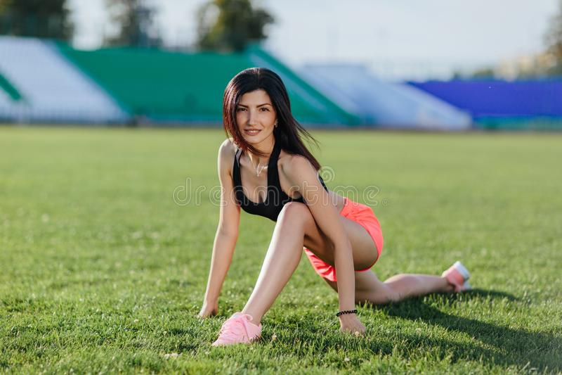 Young beautiful fitness girl doing stretching on the stadium. Summer sport activity. Green stadium grass on background. Sport and stock photography