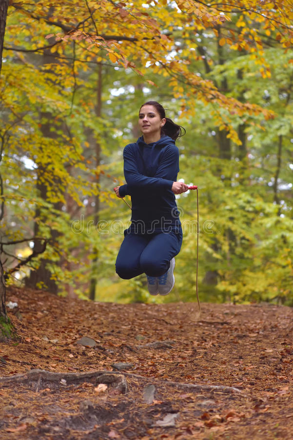 Young beautiful fitness woman skipping rope in forest, autumn co. Lors royalty free stock image