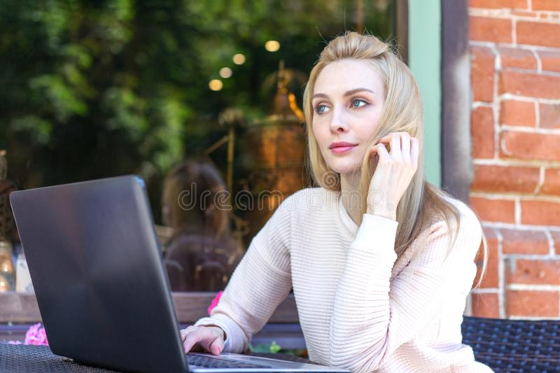 Young beautiful freelancer Caucasian girl is sitting in a street bar and working remotely on her laptop stock photos