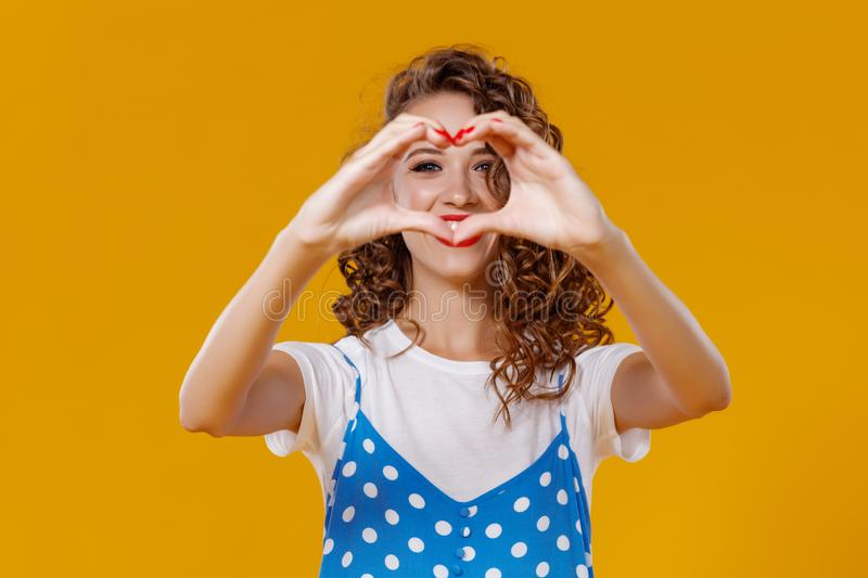 Beautiful funny girl holds hands in shape of a heart on yellow background stock photography