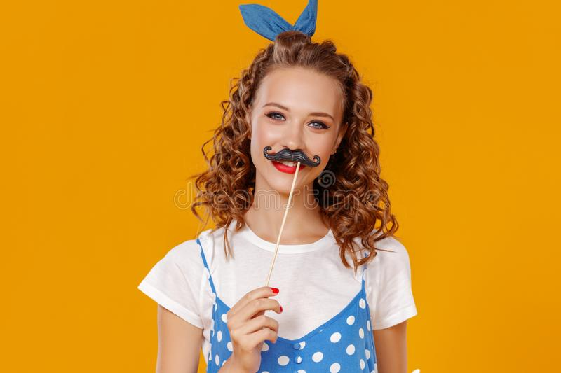 beautiful funny girl with moustache on colored yellow background stock photography