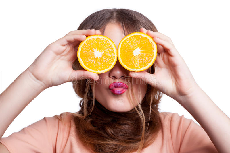 Young beautiful funny girl with orange slice and makeup and hairstyle looking at camera. royalty free stock images