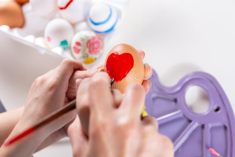 Mother and her child hands painting Easter eggs stock photo