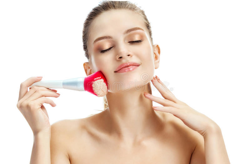 Young beautiful girl applying cosmetic powder on her face with pink make up brush. Photo of blonde girl on white background. Beauty concept royalty free stock images