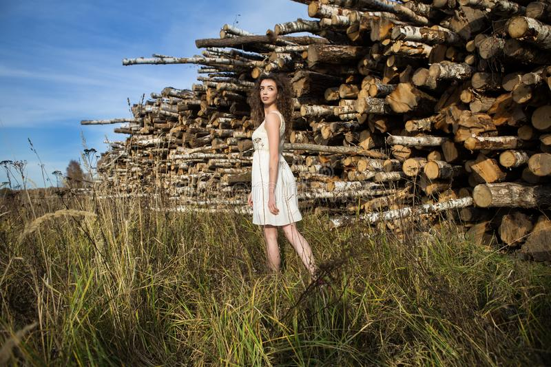 Young beautiful girl on a background of sawn trees stock image