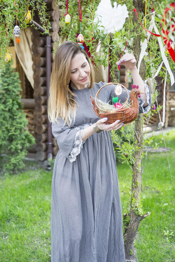 Young beautiful girl with a basket with Easter eggs on background Easter tree. With colorful decor royalty free stock images