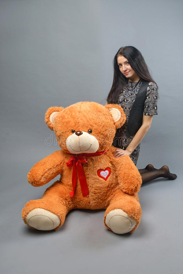 Young beautiful girl with big teddy bear soft toy happy smiling and playing on grey background stock photo