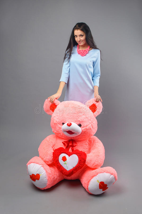 Young beautiful girl with big teddy bear soft toy happy smiling and playing on grey background stock images