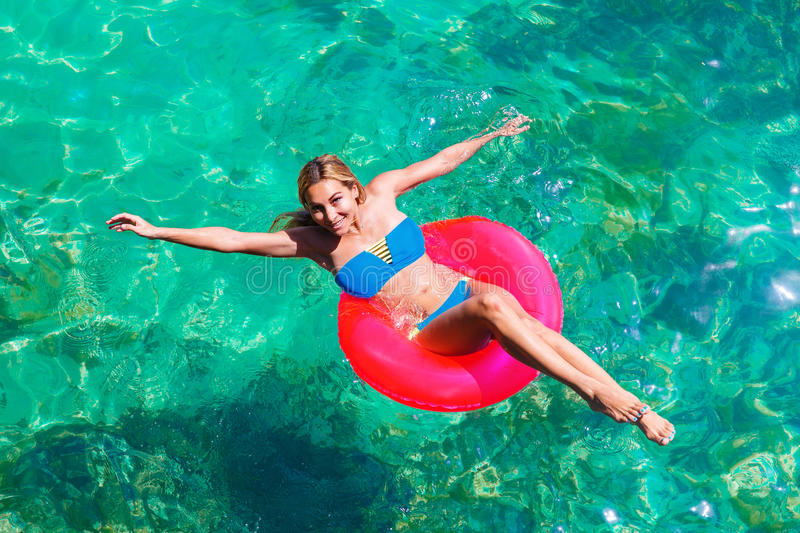 Young beautiful girl in bikini swims in a tropical sea on a rubber ring. Summer vacation concept. stock images